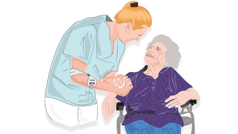 Altenpflegerin trägt Masalo Manschette MED bei der Arbeit und hält die Hand einer älteren Dame